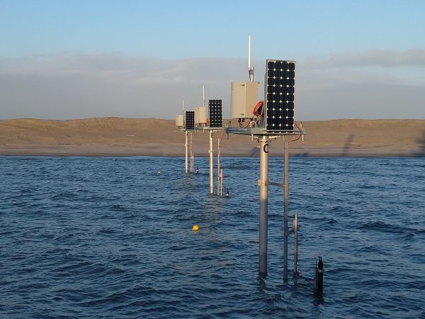 Three of the smaller monitoring stations in shallow water close to the coastline. Solar panels and greyish telemetry boxes are visible on the top, while semi-submerged ADCPs are visible in the waterline. (Photo: Jan-Willem Mol/Rijkswaterstaat)